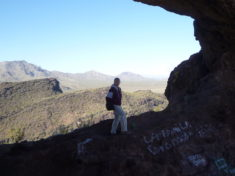 Pam in the massive arch. Eagle Eye Mountain in back (left), with Pioneer Peak beyond that.