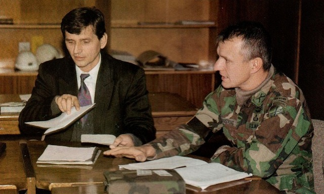 A local Bosnian official (Mr. Sefket) and the 96th CA Bn.'s Armstrong go over a list of potential basing locations for incoming American units.