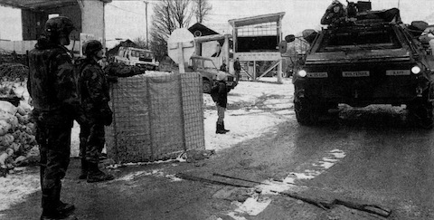 Gate guards look on as a Fox vehicle belonging to the 25th Chemical Company rolls toward the air base's front gate.