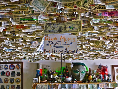 Alien knick-knacks, and maybe 20% of the bills stapled to the ceiling. Lots of military, fire & police patches as well.