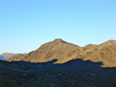 Sun just starting to shine on Maricopa Peak in the Ma Ha Tuak Range. Note the car still using its headlights on Summit Rd.