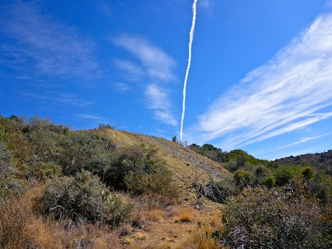 I love this shot of a contrail apparently shooting out of tailings pile.