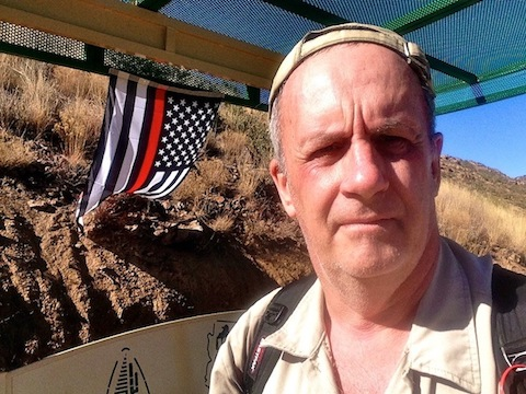 Me in front of a firefighter memorial flag hanging at the Yarnell Hill overlook.