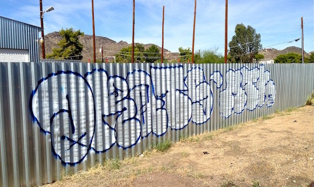 Throwup on wall of shady used car lot in Sunnyslope.